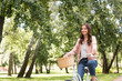 happy pretty young woman riding bicycle in park