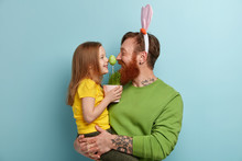 """Постер, картина, фотообои """"Lovely family play together, keep noses together on green Easter egg, enjoy pleasant moments of preparation to spring Christian holiday. Lovely female child in yellow t shirt spends time with father"""""""