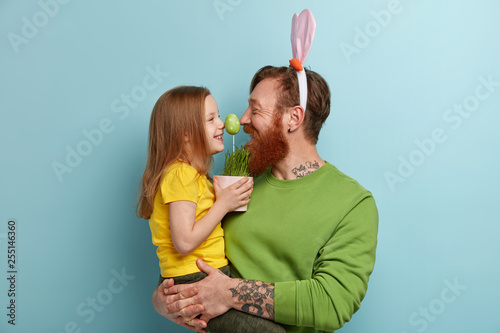 Leinwanddruck Bild Lovely family play together, keep noses together on green Easter egg, enjoy pleasant moments of preparation to spring Christian holiday. Lovely female child in yellow t shirt spends time with father