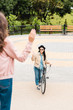 back view of girl waving hand near cheerful friend with bicycle