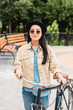 pretty girl in sunglasses and hat standing with bicycle in park