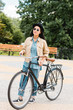 cheerful girl in sunglasses and hat standing with bicycle in park