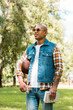 cheerful african american student in sunglasses holding books and american football