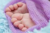 Dziecięce nogi w fioletowej narzutce.
