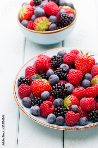 Fresh berry salad on blue dishes. Vintage wooden background. - 255156366