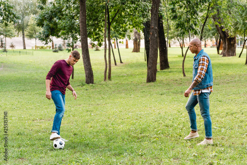 multicultural friends playing football on green grass in park
