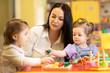 Leinwanddruck Bild - Nursery babies group playing with teacher in daycare centre playroom
