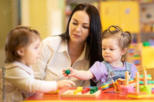Leinwanddruck Bild Nursery babies group playing with teacher in daycare centre playroom