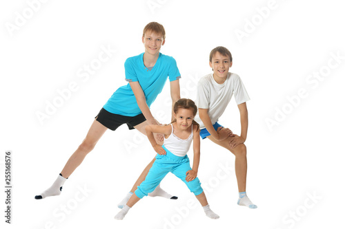 Leinwanddruck Bild Portrait of two young boys brothers and little sister exercising isolated on white background