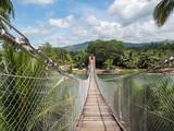 Fototapeta Bambus - Pedestrian hanging bridge over river in tropical forest, Bohol, Philippines. November, 2018 © ikmerc