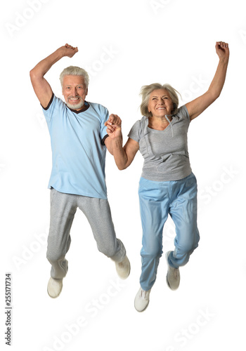Leinwanddruck Bild Portrait of senior couple jumping on a white background