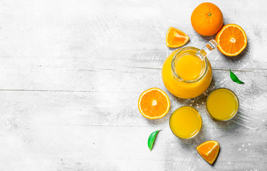 Orange juice in the pitcher and slices of fresh oranges.