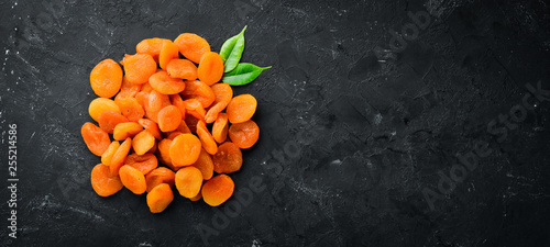 Dried apricots on a black background. Dried fruit Top view. Free space for your text. - 255214586