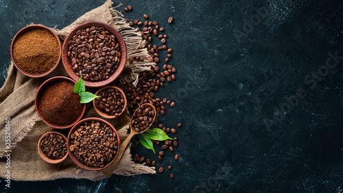 Ground coffee and coffee beans. Assortment of coffee varieties on a black background. Top view. Free space for your text. © Yaruniv-Studio
