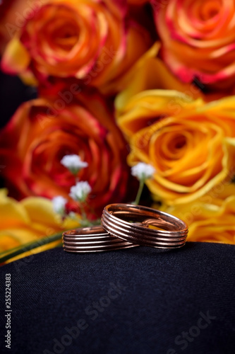 Pair of gold wedding rings and a bouquet of roses against the dark background