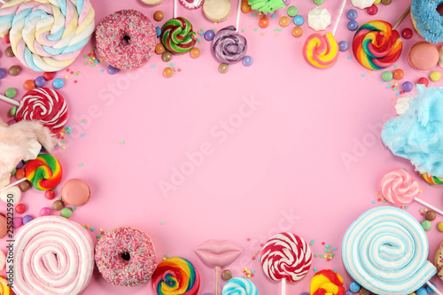 candies with jelly and sugar. colorful array of different childs sweets and treats on pink - 255225950