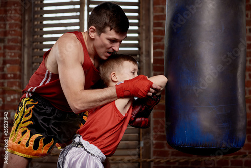 Child strikes with the hands on training gloves coach instructor. Boxing training with a coach inside the Boxing ring.