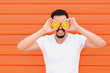 Leinwanddruck Bild - Smiling adult man with beard and moustache in white shirt pose standing against colorful wall covering eyes with two sliced pieces of orange.