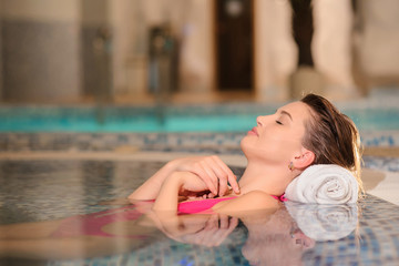 lateral view of a beautiful woman wearing swimsuits relaxing in swimming pool
