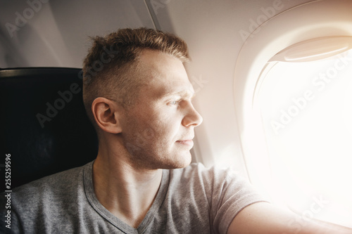 Happy tourist man makes selfie photo in cabin aircraft airplane before departure. Travel concept
