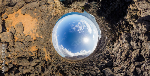 Spherical inverse little planet panorama of the rocky coast of the island of Tenerife with a mountain in the background - 255268331