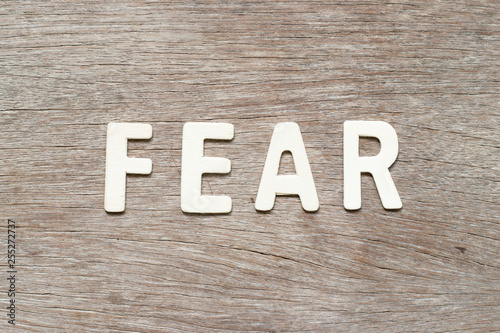 Alphabet letter in word fear on wood background