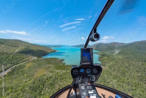 Leinwanddruck Bild Helikopter beim Anflug einer Bucht über den Whitsunday Island