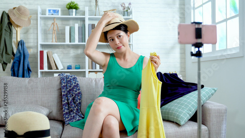 Joyful woman maintaining fashion blog. young asian girl wearing straw hats holding yellow dress showing to smartphone recording video online for vlog. beautiful famous lady review summer clothes.