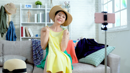 Confident female fashion blogger presenting straw hat match with yellow summer party dress to cellphone with tripod. young asian girl shop owner smiling showing clothes selling online live streaming