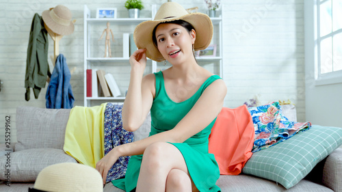 adorable female model dressed in summer straw hat recording fashion video at home. asian woman blogger shares news with followers in live streaming. confident young vlogger smiling to fans.