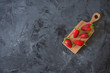 red strawberries on wooden plate on black background , top view , flatlay with copy space  - 255305759