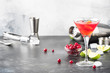 Classic alcoholic cocktail cosmopolitan with vodka, liqueur, cranberry juice, lime, ice and orange zest, gray bar counter background, bartender tols, space for text - 255309595