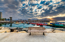 """Постер, картина, фотообои """"Coastal landscape with a wooden bench on stone walking pier as foreground, Eilat, Israel"""""""