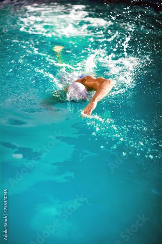Leinwanddruck Bild young athlete swimmer recreating on outdoor