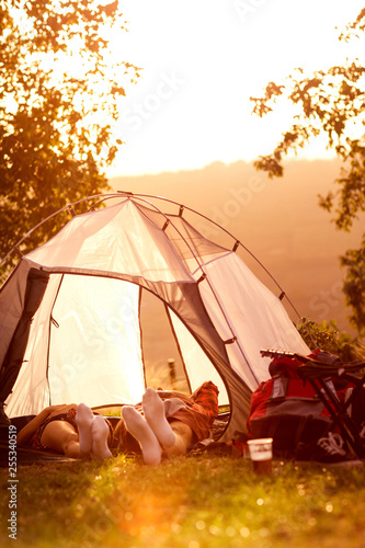 Leinwanddruck Bild Tired couple lying in tent