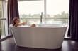 Leinwanddruck Bild - Attractive woman lying in bathtub..