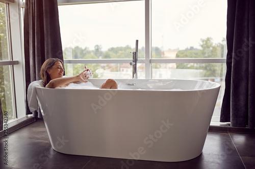 Leinwanddruck Bild Attractive woman lying in bathtub..