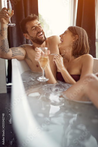 Leinwanddruck Bild Couple Relaxing In Bubble bath and drinking champagne.