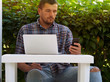 A man sits with a laptop outdoors.