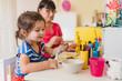 Leinwanddruck Bild - granddaughter doing handycraft together with her grandmother in nursery, improvement of fine motor skills