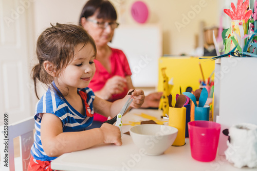 Leinwanddruck Bild granddaughter doing handycraft together with her grandmother in nursery, improvement of fine motor skills