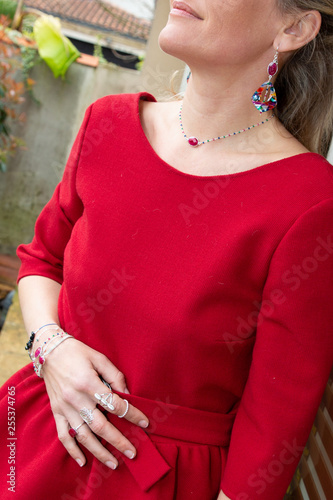 beautiful woman with red earring, ring and pendant outdoor in red dress fashion