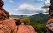 canvas print picture - looking through rock formations over a beautiful landscape with blue sky and clouds