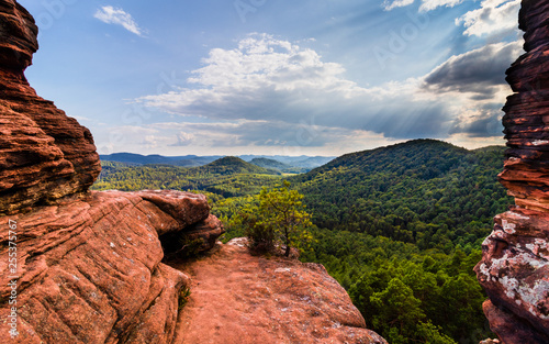 canvas print picture looking through rock formations over a beautiful landscape with blue sky and clouds