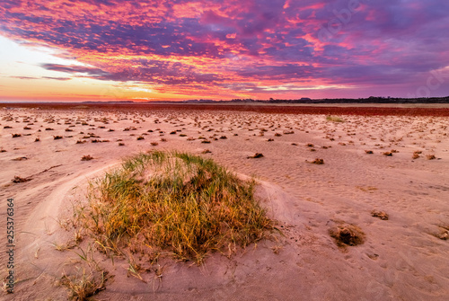 purple clouds on a sunrise at the beach with structure in the sand
