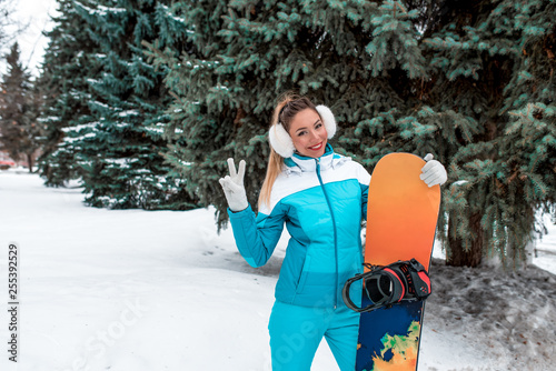 obraz lub plakat Beautiful girl blue jumpsuit, in winter at resort, a combined board. Resting in warm white ears cap. Snow and drifts on background. Happy smiling and posing holding a board. Free space for text.