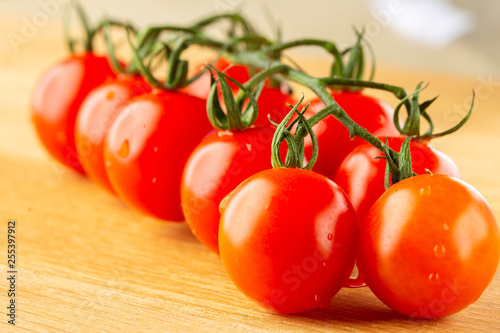 Branch of raw cherry tomatoes lying on wooden board and looking good