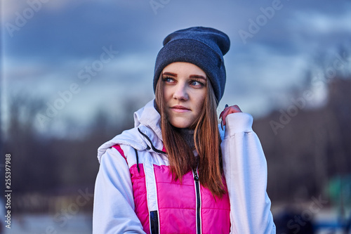 Portrait of a young beautiful girl with dark brown hair in a sports hat and jacket in the first rays of the morning rising sun in an autumn cold morning.