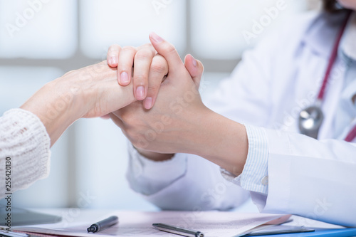 Medical doctor reassuring patient by holding patient's hands in hospital setting