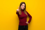 Woman with turtleneck over yellow wall showing and lifting a finger